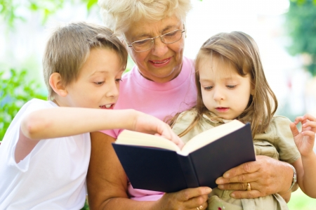 Grandmother reading  a book for grandchildren, outdoors Фото со стока - 21767785