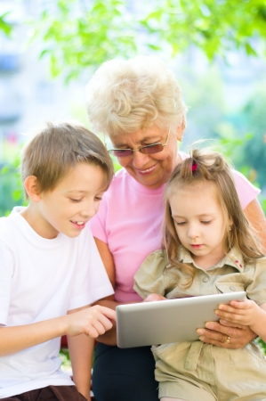 happy grandmother with grandchildren using tablet PC, outdoors