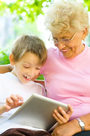 little boy with his grandmother using tablet PC, sitting in the park photo