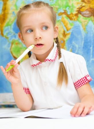 Cute little girl is writing using a pen in preschool Фото со стока