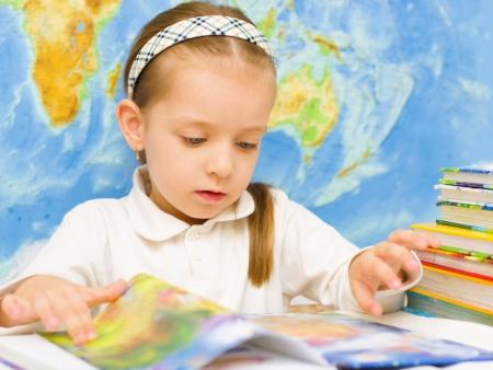 Cute little girl is reading a book in front of world map in preschool Фото со стока