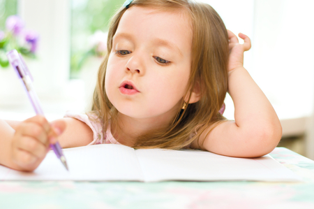 writing activity: cute happy little girl writing something in her notebook