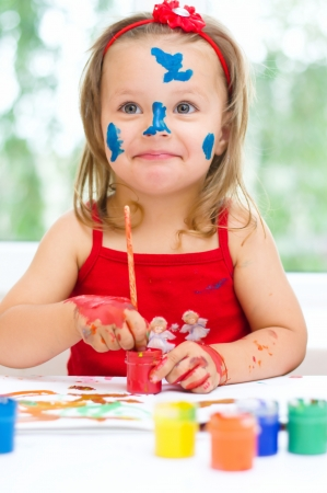 finger paint: little girl painting with paintbrush and colorful paints
