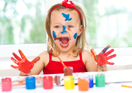 caritas pintadas: pintura de la niña con pincel y pinturas de colores Foto de archivo