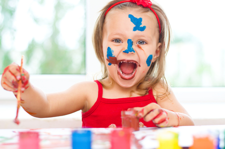 little girl painting with paintbrush and colorful paints