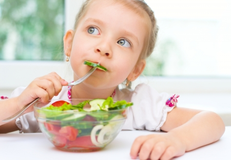 Little cute girl eating vegetable salad