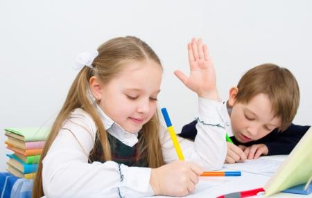 Little schoolchildren writing in workbook photo
