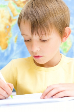 schoolboy writing in his workbook using a pen in front of world map photo