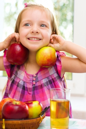 cute little girl holding apples at home Фото со стока