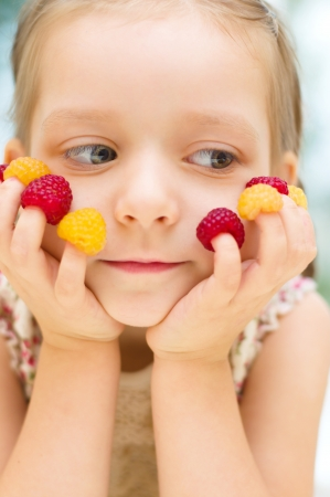 kids eating healthy: Happy little girl with raspberries at home