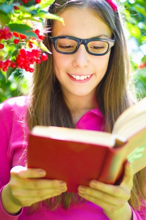 Cute teenage girl is reading a book while wearing glasses outdoors photo