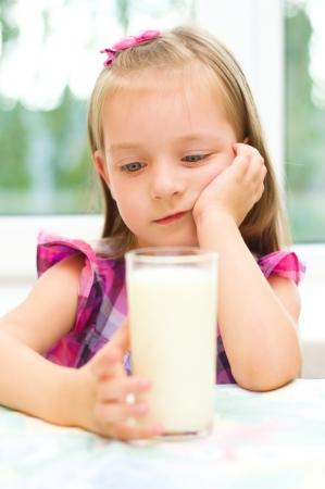 Sad little girl refuses to drink a glass of milk Фото со стока