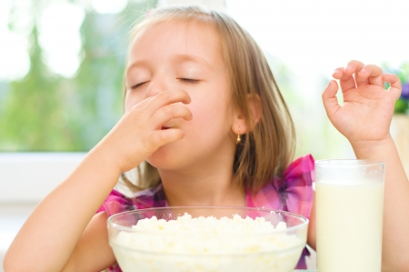 Healthy food. Cute little girl is eating cottage cheese, curd with milk photo