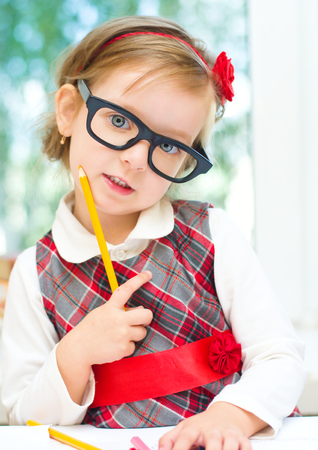 girl glasses: cute little girl is playing with crayon Stock Photo