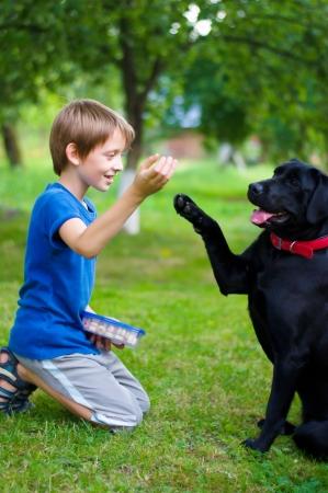 Niño juega con el perro negro al aire libre Foto de archivo - 22932992