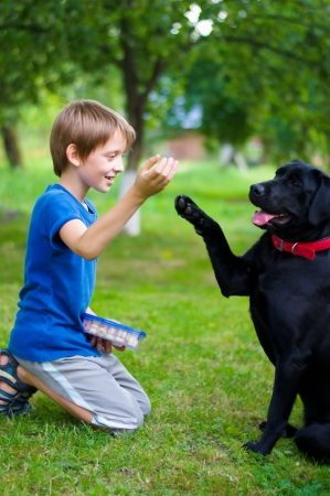 Young boy plays with black dog outdoors Фото со стока