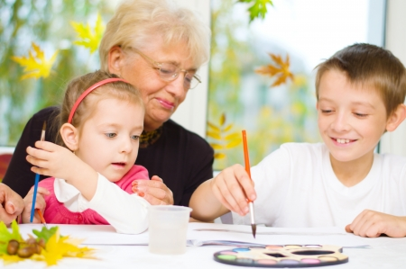 three children: Grandmother with grandchildren painting with paintbrush and colorful paints, autumn background Stock Photo