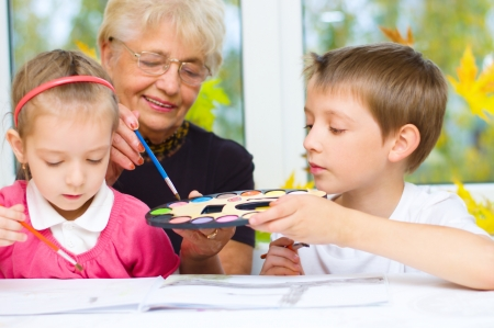 Grandmother with grandchildren painting with paintbrush and colorful paints, autumn background Standard-Bild