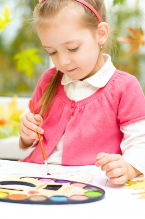 little girl painting with paintbrush and colorful paints, autumn background photo