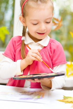 little girl painting with paintbrush and colorful paints, autumn background Фото со стока