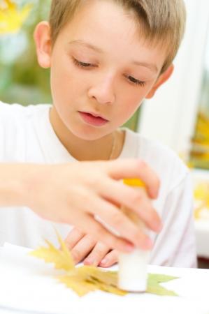 resistol: niño aplicando un arce de hojas secas con pegamento al hacer artes y oficios en la escuela Foto de archivo