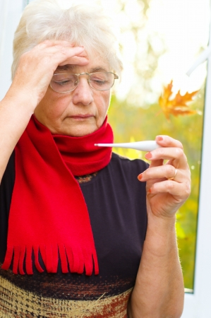 Old woman taking her temperature, autumn background Фото со стока - 22993452
