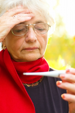 Old woman taking her temperature, autumn background