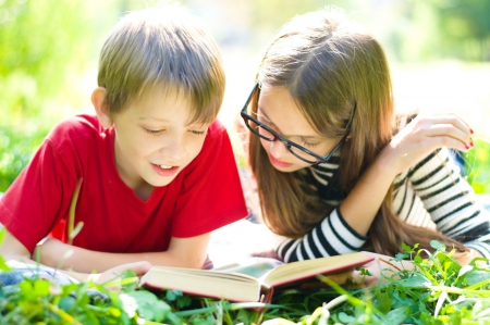 Kids reading together enjoying a book laying on the grass outdoors Standard-Bild