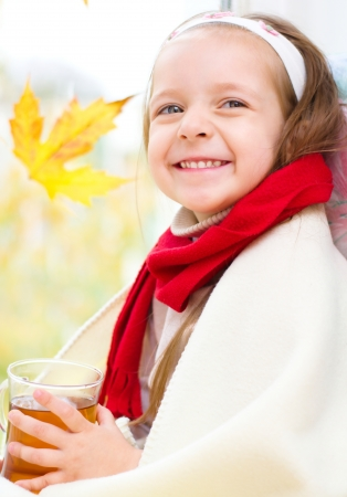 little girl drinking tea while sitting on the window Stock Photo - 23325320
