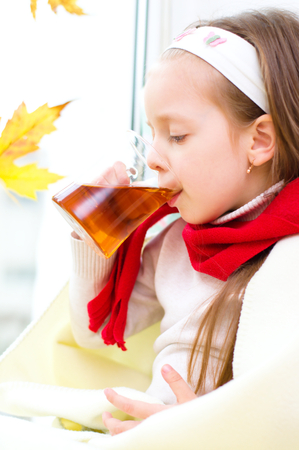 little girl drinking tea while sitting on the window Stock Photo - 23325322