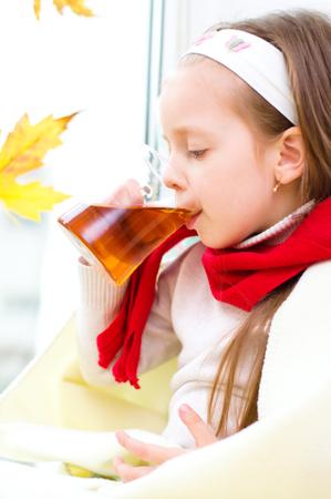 little girl drinking tea while sitting on the window Stock Photo - 23325322
