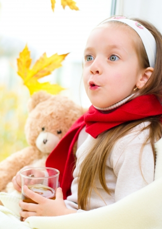 little girl drinking tea while sitting on the window Stock Photo - 23325323