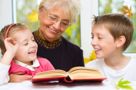great grandmother: Great-grandmother reading a book for grandchildren at home