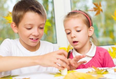 pegamento: niña con su hermano, la aplicación de un arce de hojas secas con pegamento al hacer artes y oficios