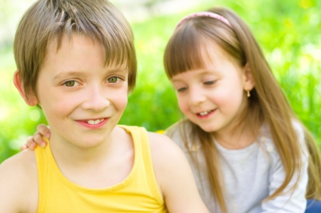 Summer portrait of a happy little girl hugging her brother outdoors photo