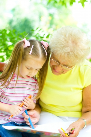 little girl with her grandmother drawing using crayons outdoors photo