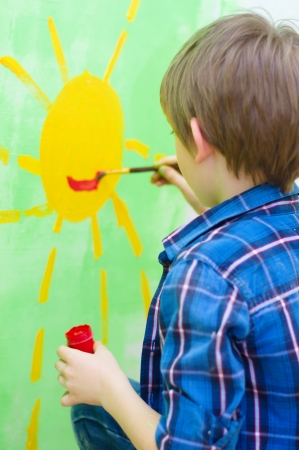 cute boy painting happy sun on the wall at home Stock Photo