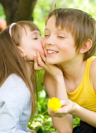 Cute little girl gives her brother a kiss on the cheek outdoors photo