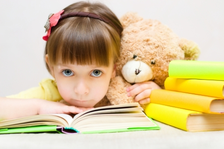Cute little girl play with book and toy bear while sitting at table