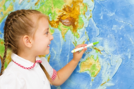 happy little girl smiles by world map photo