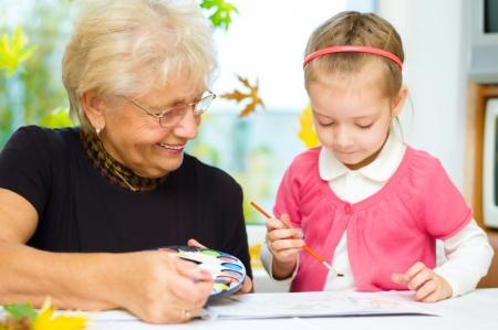 Abuela con la nieta de pintura con pincel y pinturas de colores, fondo de otoño Foto de archivo - 23957063