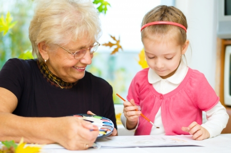 Grandmother with granddaughter painting with paintbrush and colorful paints, autumn background