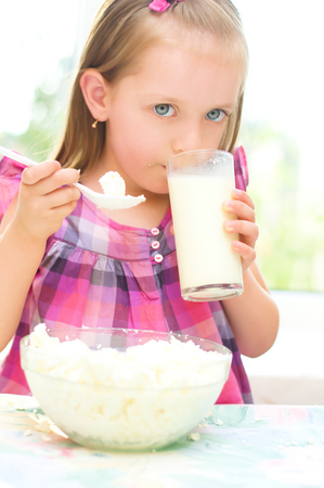 healthy food, child is eating cottage cheese, curd and drinking milk