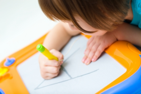 Little girl writing at magnetic drawing board Standard-Bild