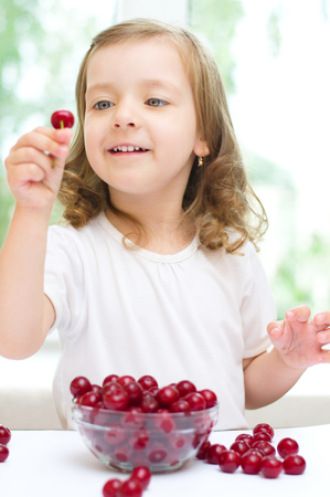 little girl with cherry berries bowl indoors