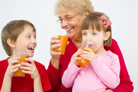 happy grandmother with grandchildren drinking fruit juice at home photo