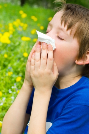 Little boy is blowing his nose outdoors