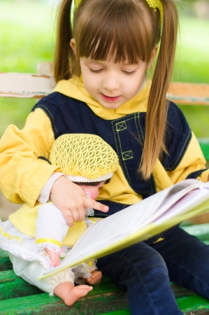 pretty little girl reads a book with her doll at the park photo