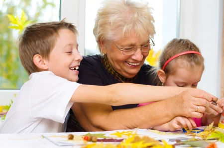 Grandmother with grandchildren applying a dry maple leaves using glue while doing arts and crafts Standard-Bild