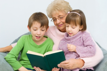 Grandmother reading a book for grandchildren at home